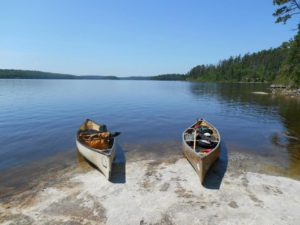 Image of two canoes sitting just on the edge of a lakeside